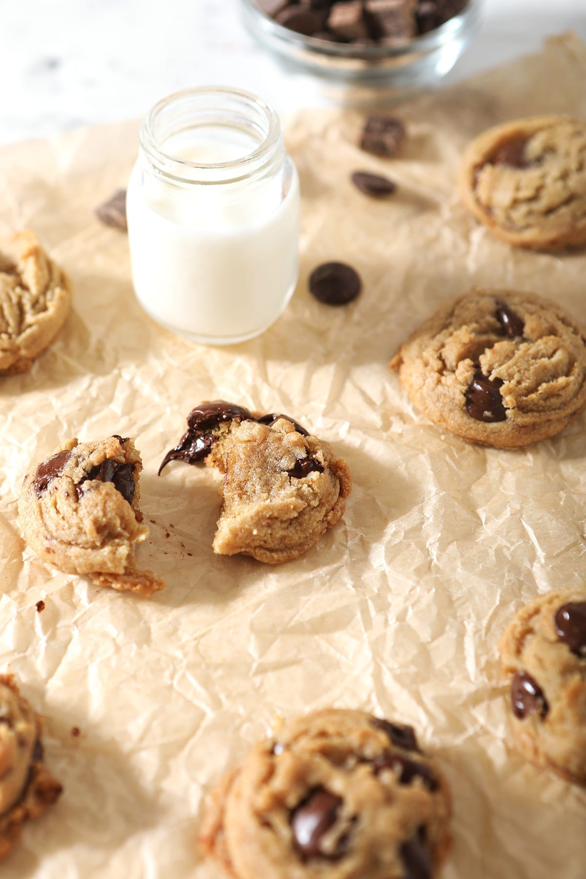 Cookies, fresh out of the oven, are shown on brown paper with shot glasses of milk