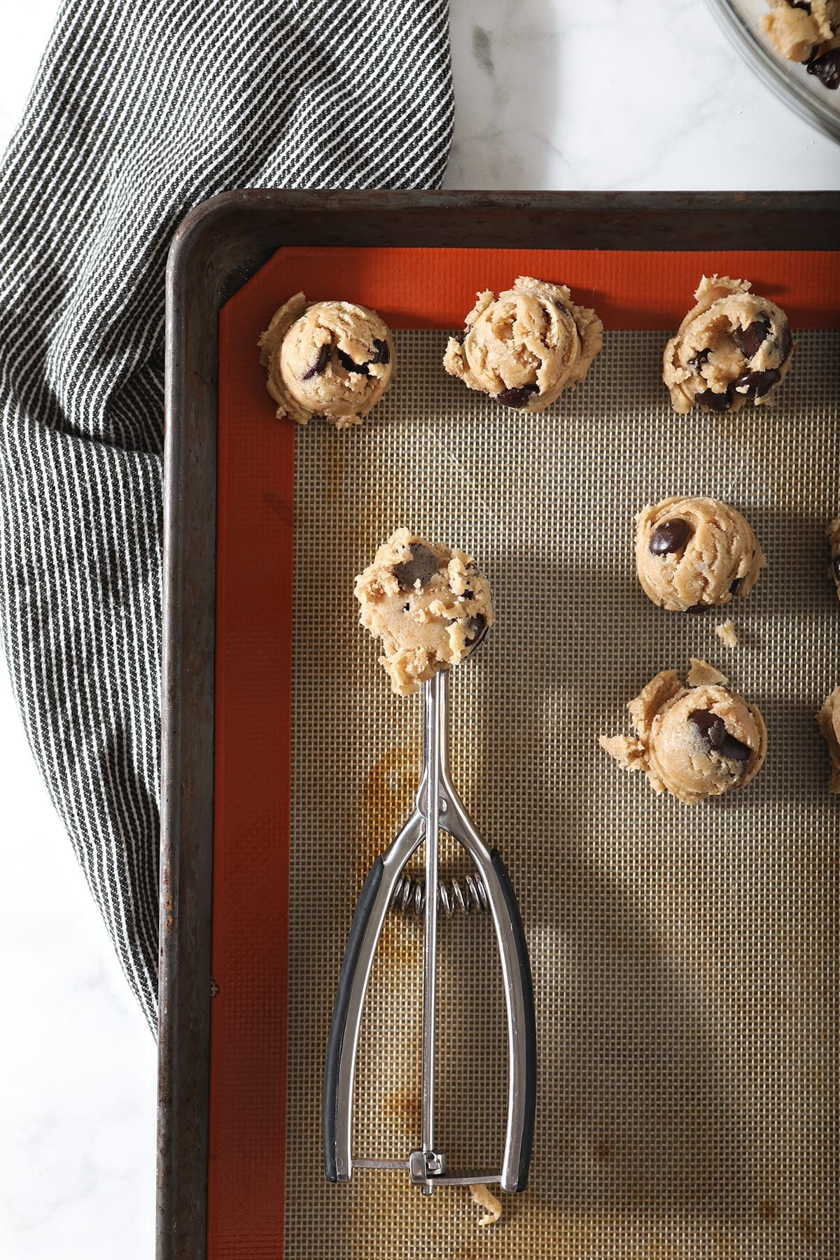 A cookie scoop has some cookie dough inside it, as it scoops cookies onto a prepared baking sheet
