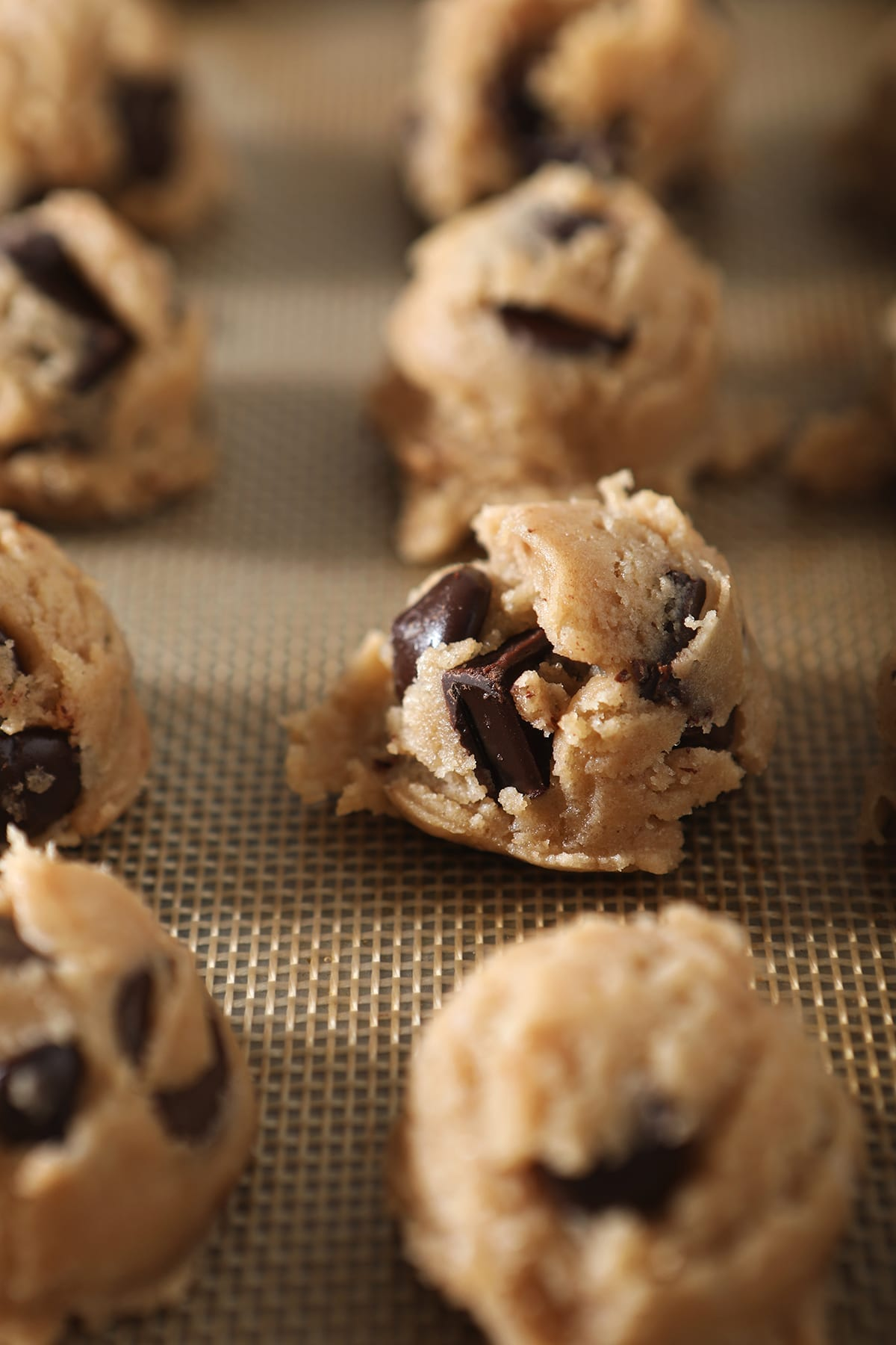 Chocolate Chip Cookie Dough, in scoops, is shown on a baking sheet before it chills