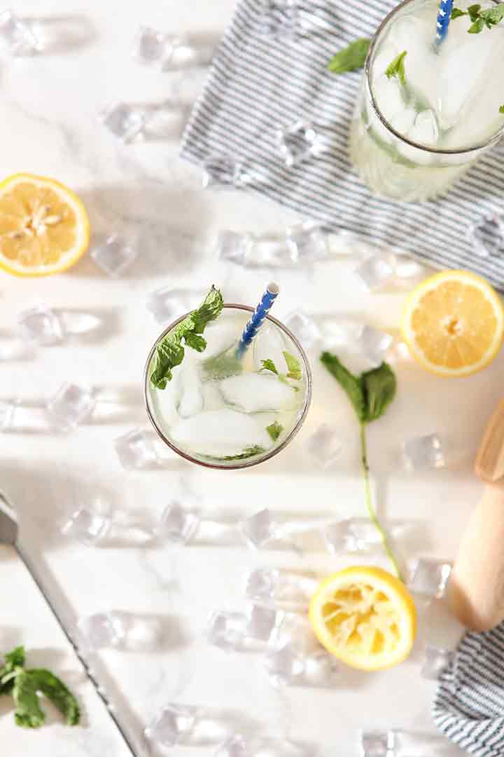Overhead of a glass of Mint Lemonade, surrounded by ingredients