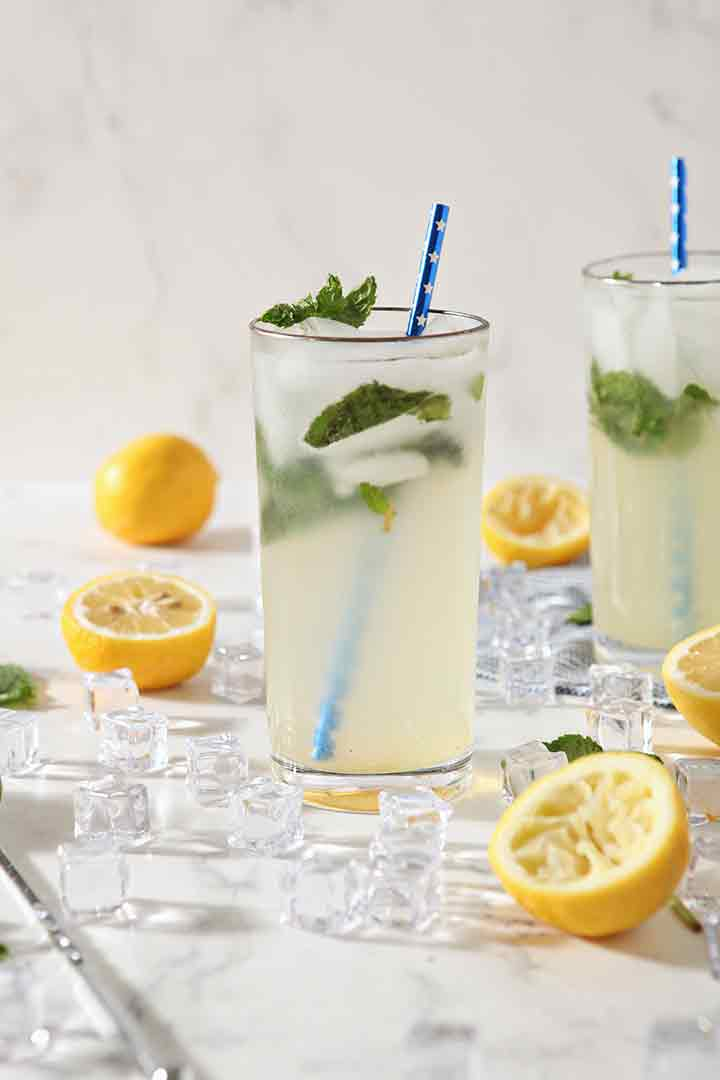 Two glasses of Mint Lemonade are ready for drinking, surrounded by ice, lemons and mint leaves