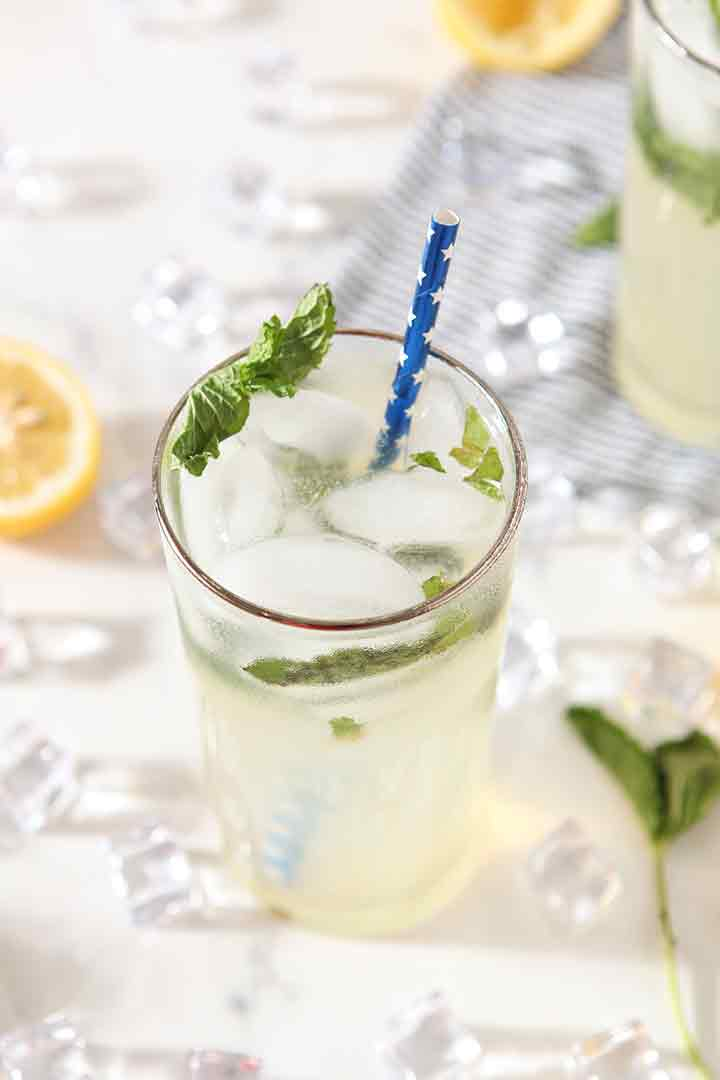 Close up of Mint Lemonade in a glass, surrounded by ice