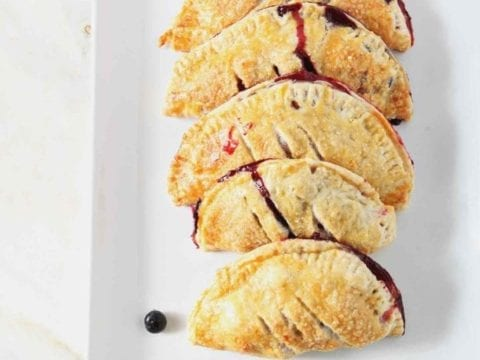 Strawberry and Blueberry Hand Pies sit on a white platter, surrounded by fresh blueberries and strawberries, before serving.