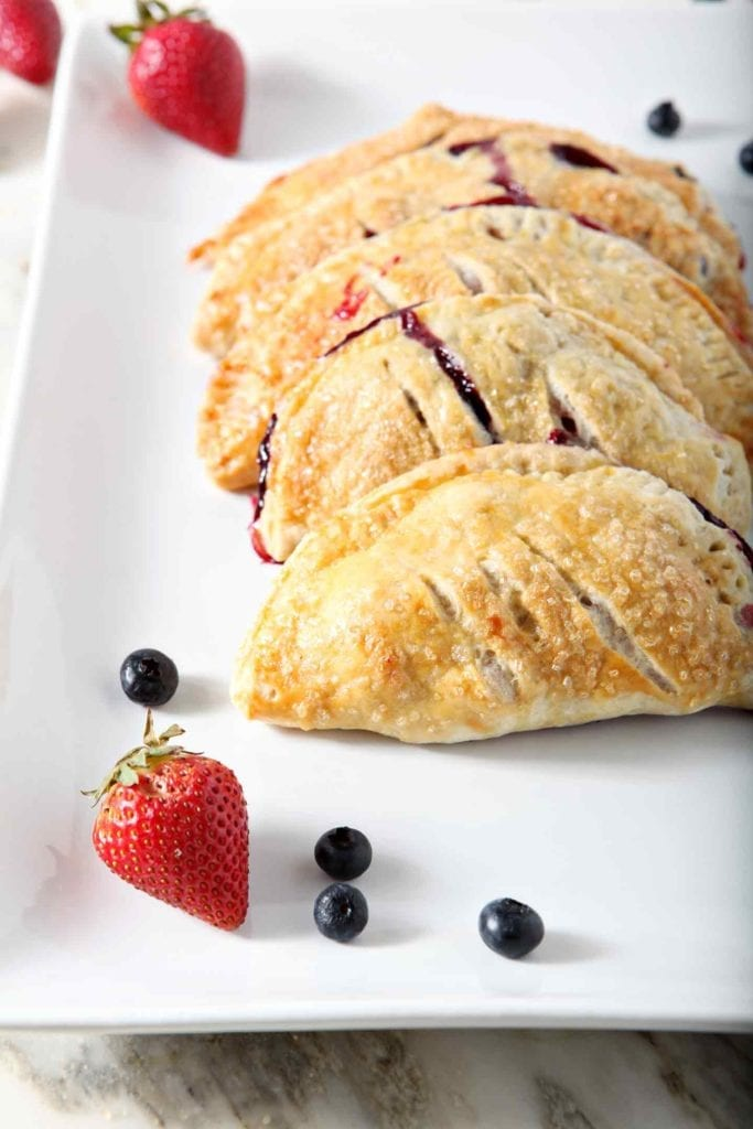 Several Hand Pies are stacked on a plate, surrounded by fresh strawberries and blueberries, before serving