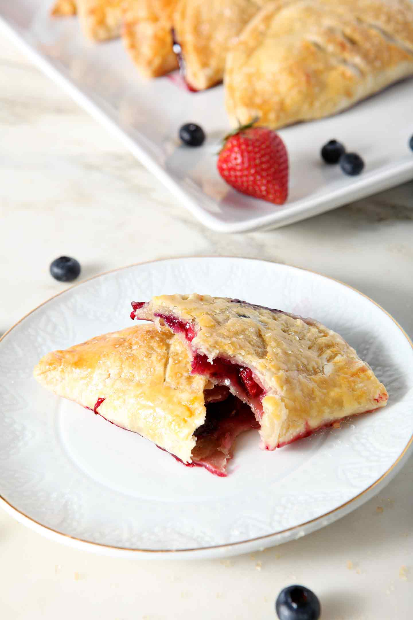 A Strawberry and Blueberry Hand Pie, broken in half, sits on a white dessert plate, with a platter of additional hand pies behind it.