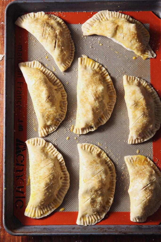 Unbaked individual pies sit on a baking sheet, brushed with egg wash and sprinkled with sugar, before baking.