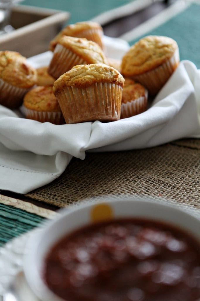 A basket holds a serving of Honey Jalapeño Cornbread Muffins, perfectly paired with a bowl of chili, shown in the foreground