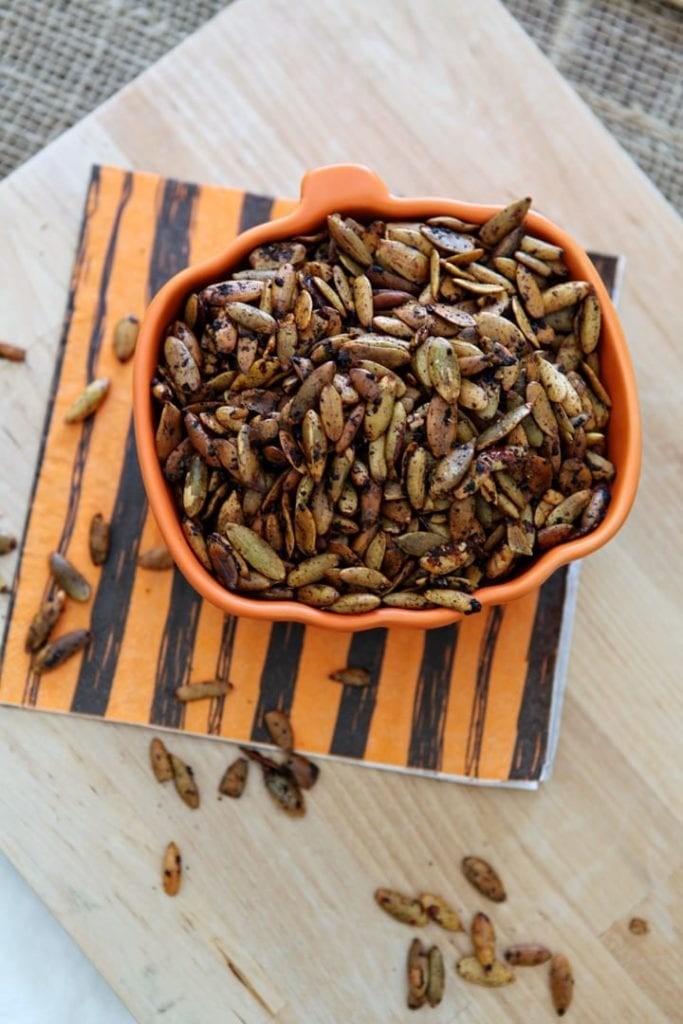 Roasted Pumpkin Seeds are displayed in a pumpkin-shaped bowl on a wooden background