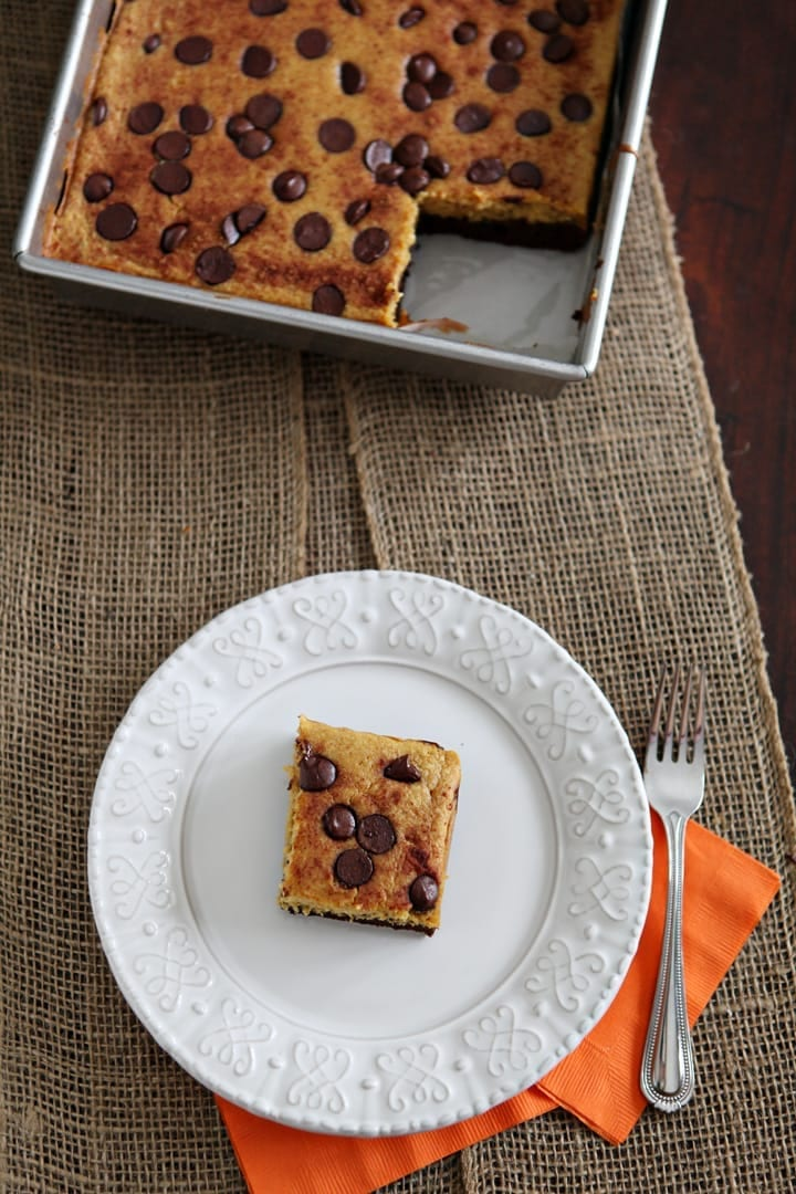 A white plate holds a pumpkin bar next to a fork and the pan holding the rest of the brownies