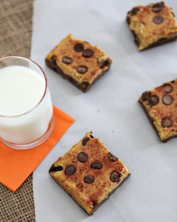 Overhead of pumpkin cheesecake bars on a white piece of parchment with a glass of milk