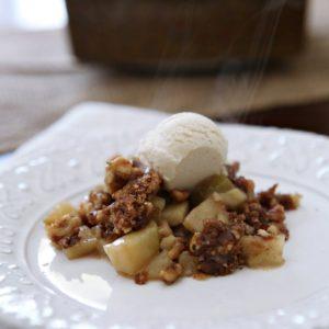 Apple dessert with scoop of ice cream on white plate