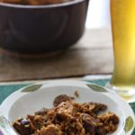 A bowl of Chicken and Sausage Jambalaya sits next to a beer on a table