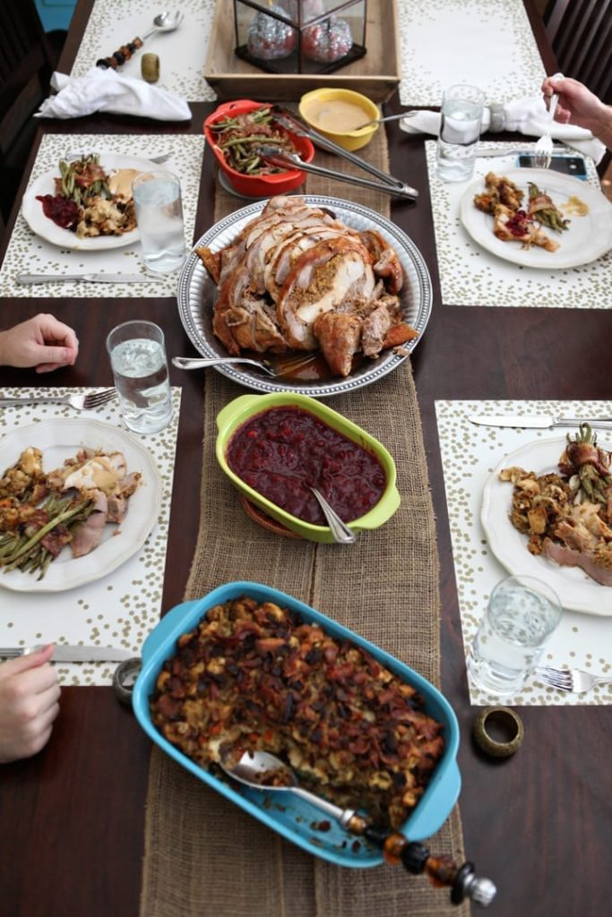 A Friendsgiving table lined with dishes before guests begin eating