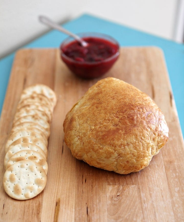 Bread, crackers and cranberry chutney on wood cutting board