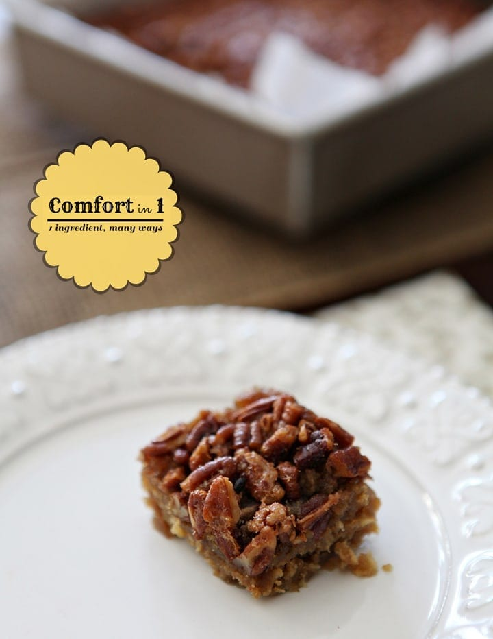 A pecan pie bar on a white plate in front of a square baking pan