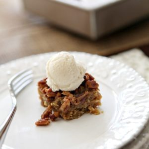 A Drunken Pecan Pie Bar sits on a white plate with the baking dish in the background