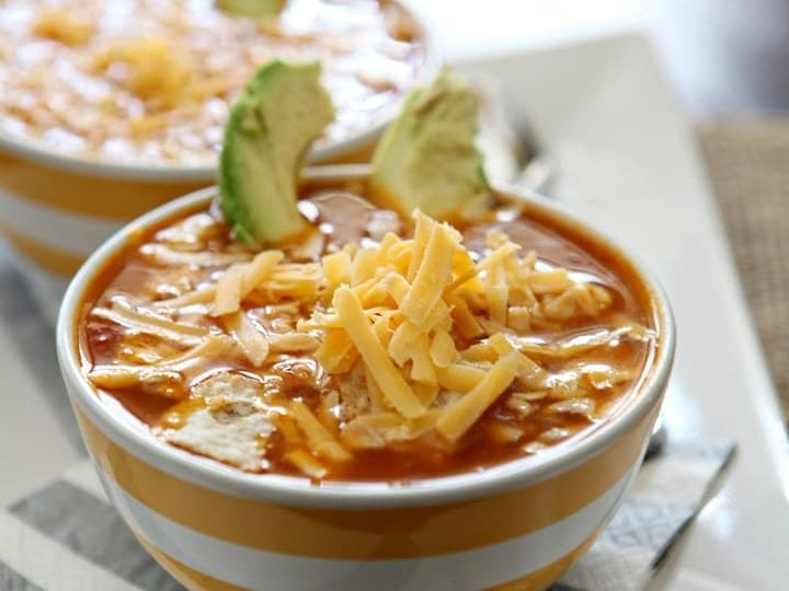 Two bowls of Turkey Tortilla Soup are garnished with cheddar cheese and avocados