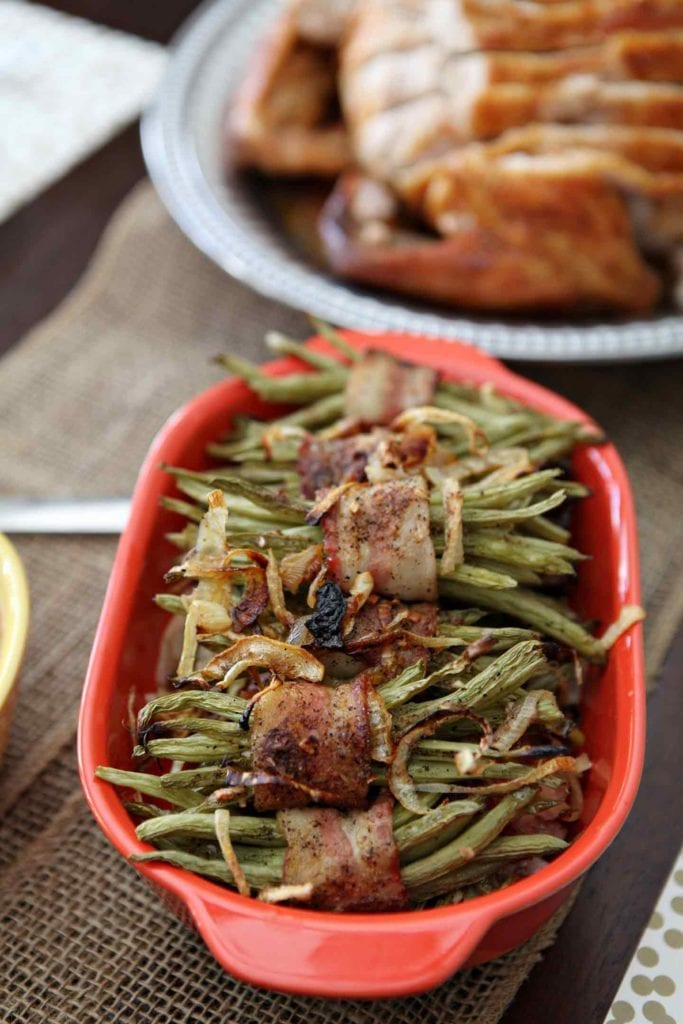 A red serving dish holds several Green Bean Bacon Bundles on a holiday table
