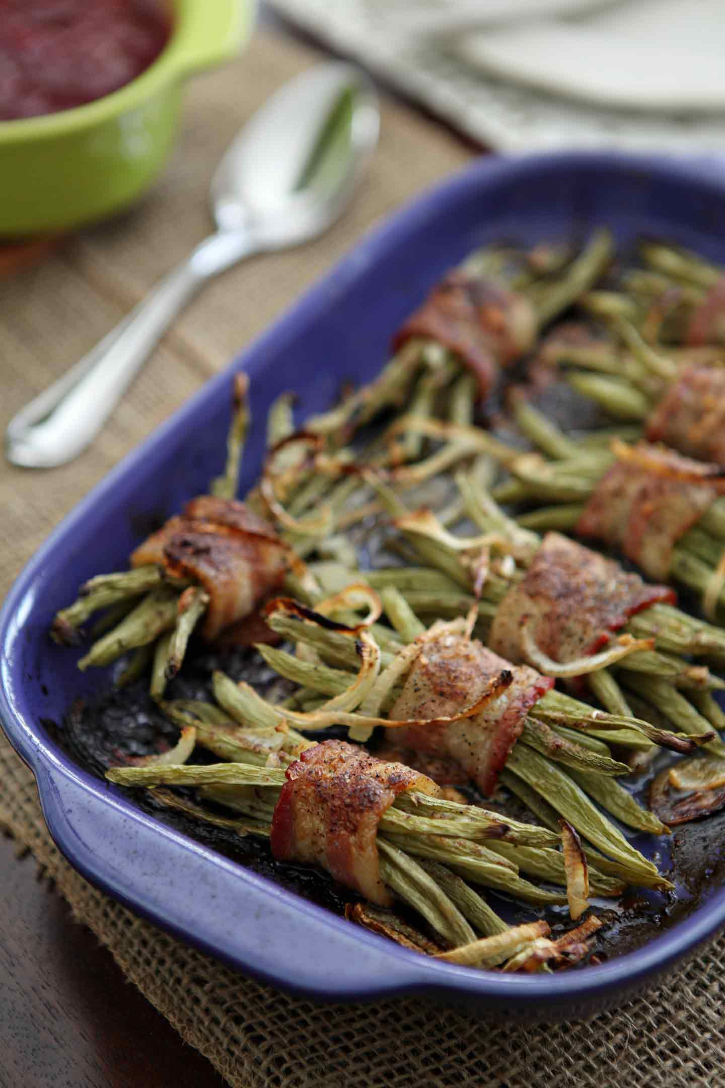A platter of Green Bean Bacon Bundles sits on a Thanksgiving table