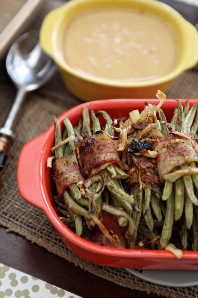 Several Green Bean Bacon Bundles sit in a red baking dish and are served alongside gravy at a holiday table