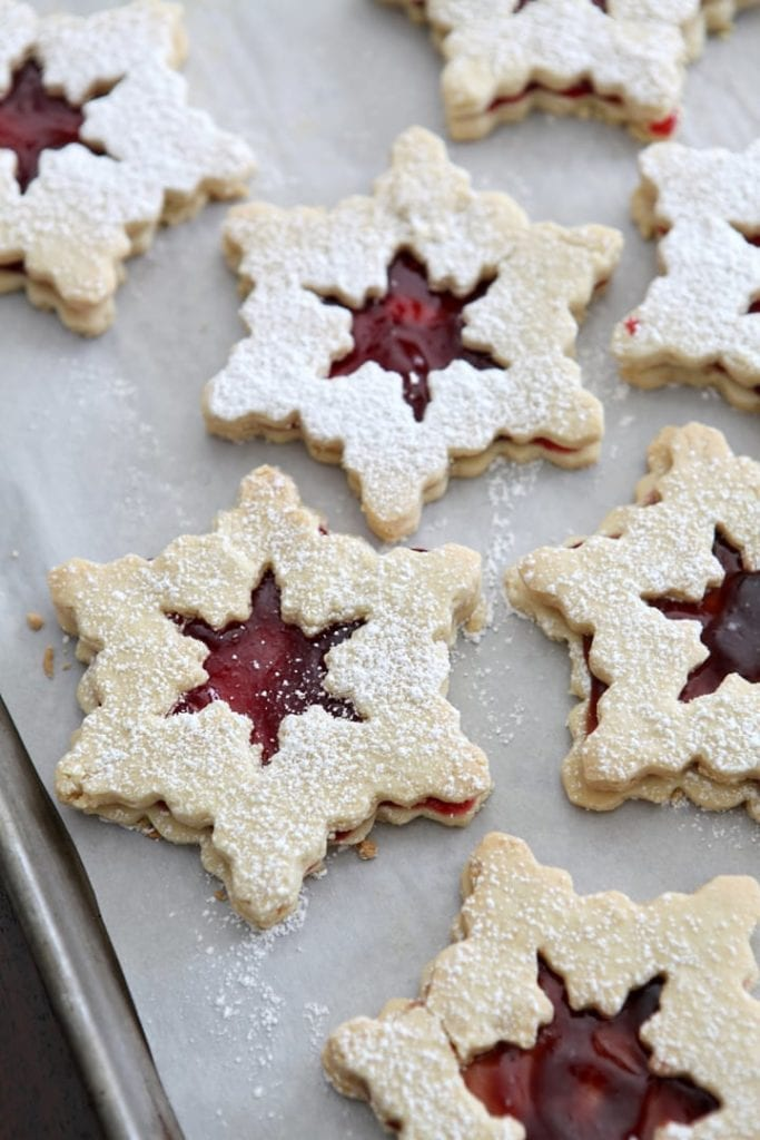 A baking sheet holding completed Raspberry Linzer Snowflake Cookies is dusted with powdered sugar before serving