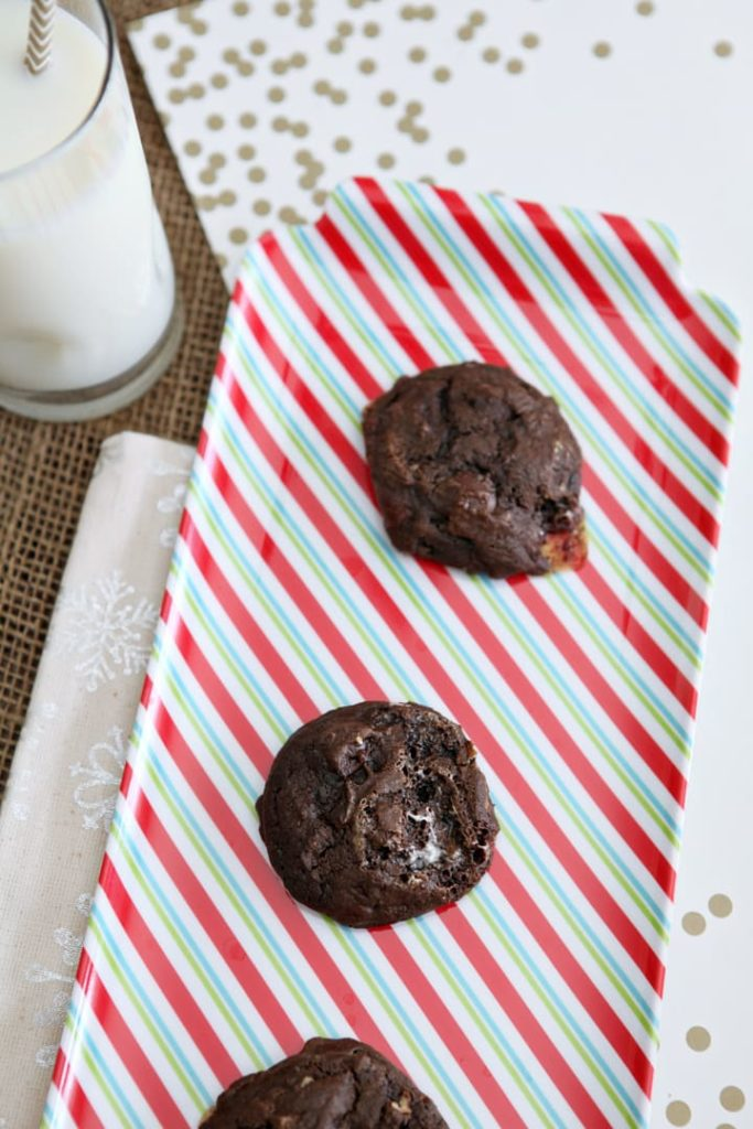 Overhead of Chocolate Marshmallow Cookies with Pecans on a red, green and white striped platter by a glass of milk