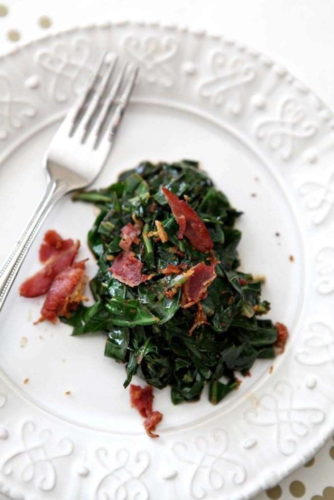 Bacon Collard Greens, served on a white plate, and topped with additional bacon