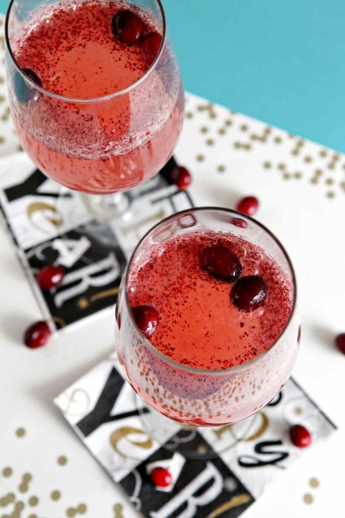 Two Cranberry Sparkler Mocktails are shown from above, surrounded by New Year's Eve decor