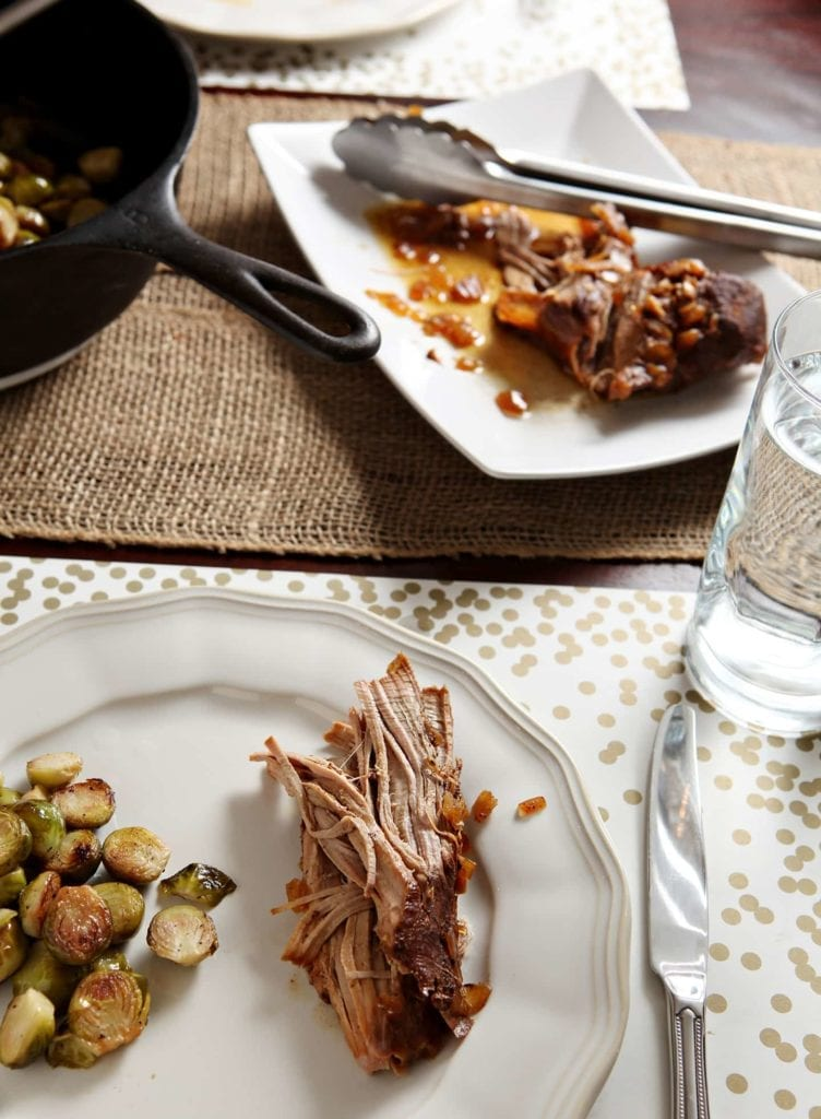A serving of shredded pork tenderloin on a white plate with brussels sprouts and more pork on the table in front of it