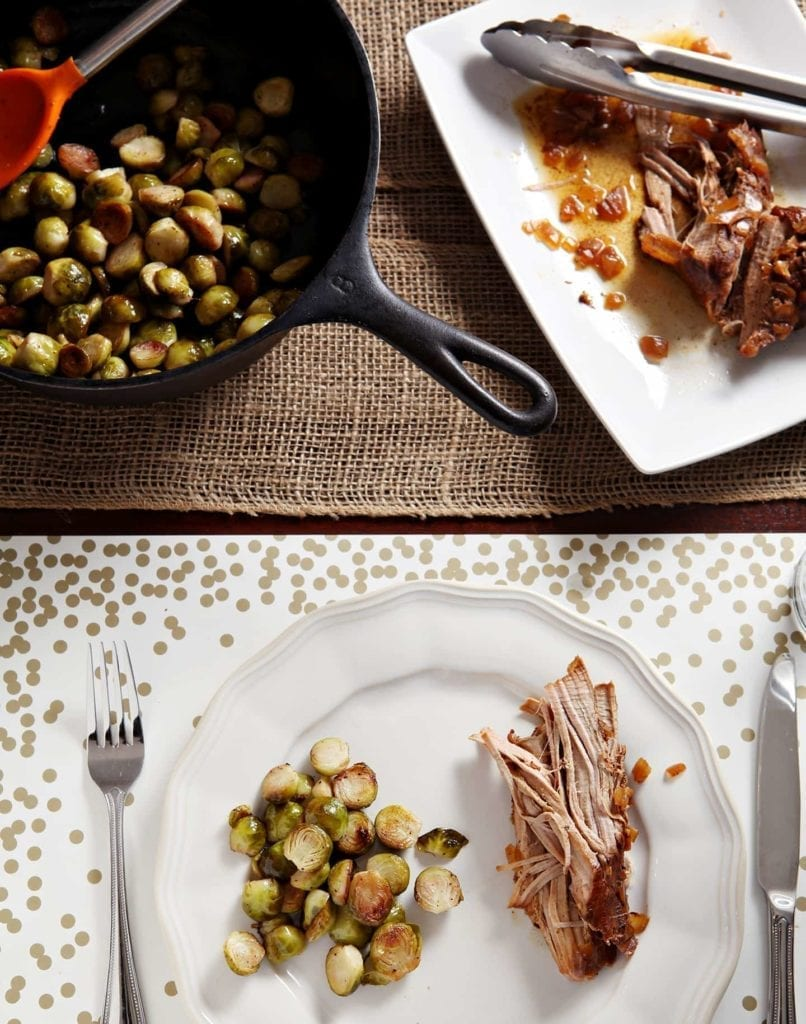 A white plate holds brussels sprouts and pork, with more brussels sprouts in a skillet and a white platter of pork are shown on the tabletop