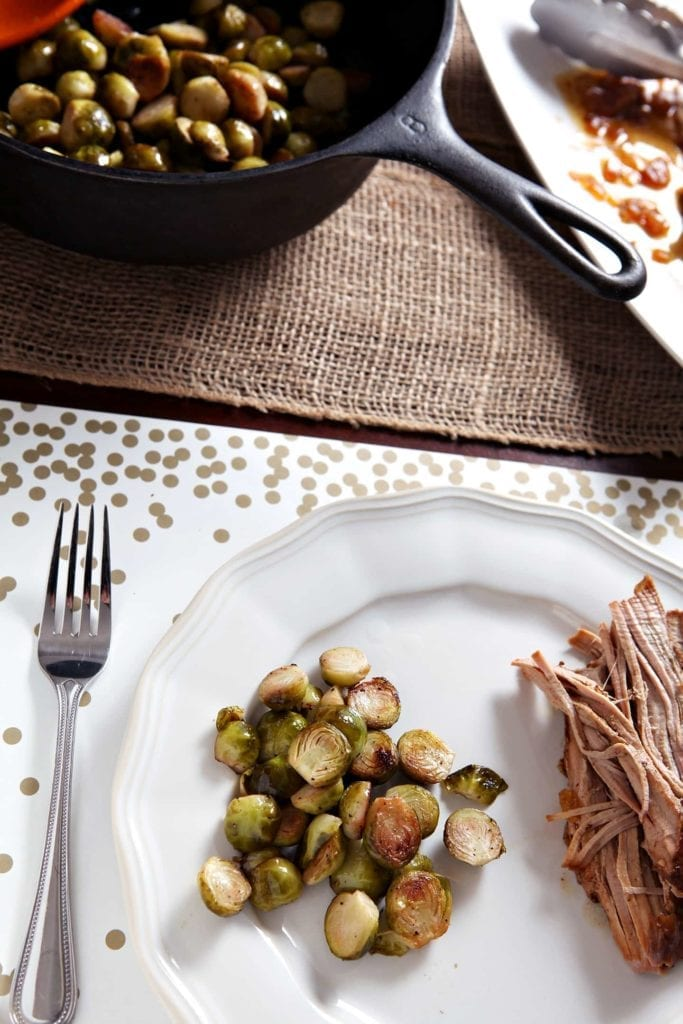A serving of Lemon Brussels Sprouts on a white plate beside a serving of slow cooker pork tenderloin