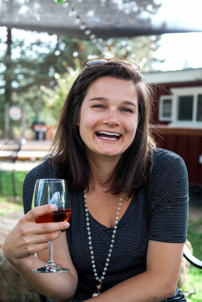 A woman sits beneath an awning, laughing while holding a glass of red wine