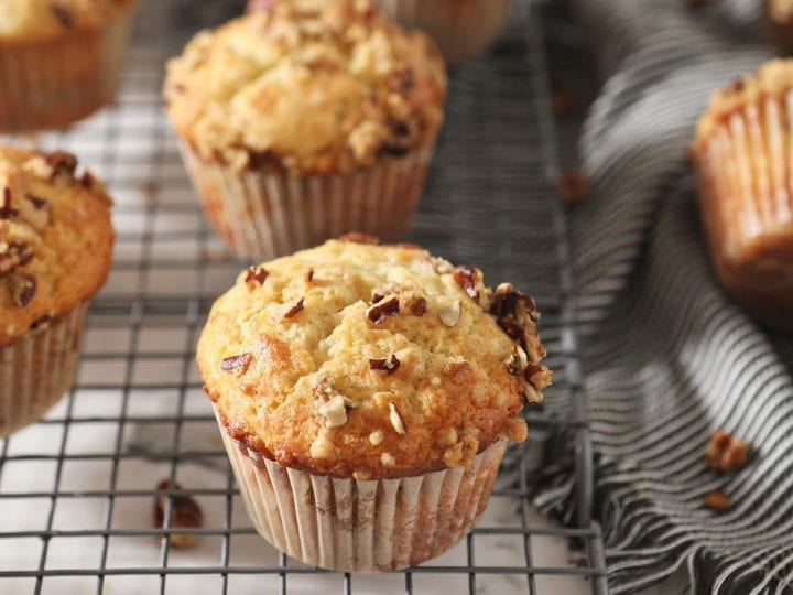 Coffee Cake Muffins sit on a wire cooling rack next to a gray striped towel