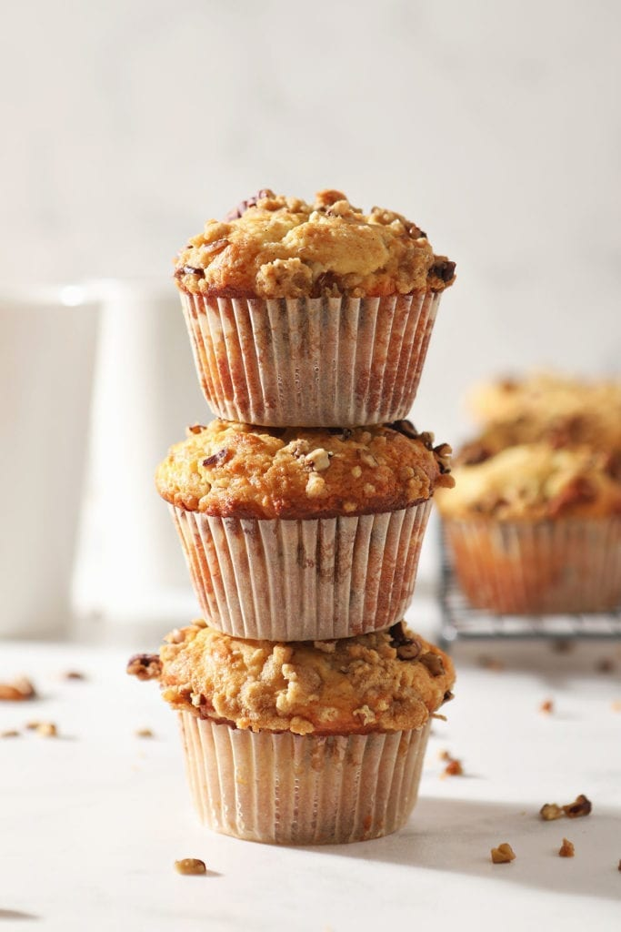 Three Coffee Cake Muffins are stacked on top of each other in front of a coffee mug and a wire cooling rack holding more muffins