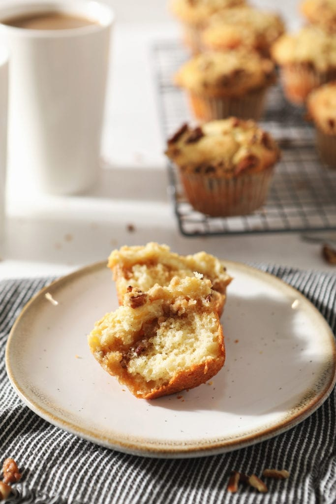 A halved Coffee Cake Muffin sits on a pottery plate in front of coffee mugs and a wire cooling rack holding more muffins