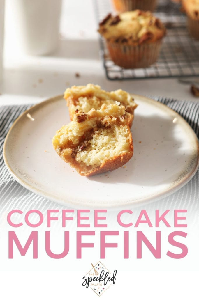 A halved Coffee Cake Muffin sits on a pottery plate in front of coffee mugs and a wire cooling rack holding more muffins with the text 'coffee cake muffins'