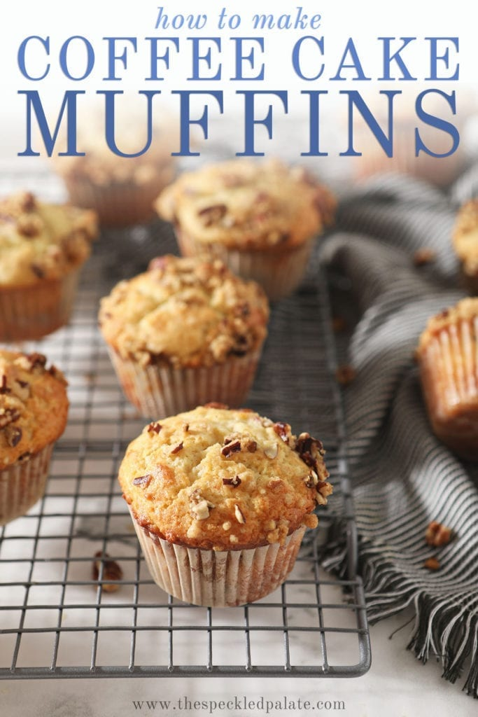 Coffee Cake Muffins sit on a wire cooling rack next to a gray striped towel with the text 'how to make coffee cake muffins'