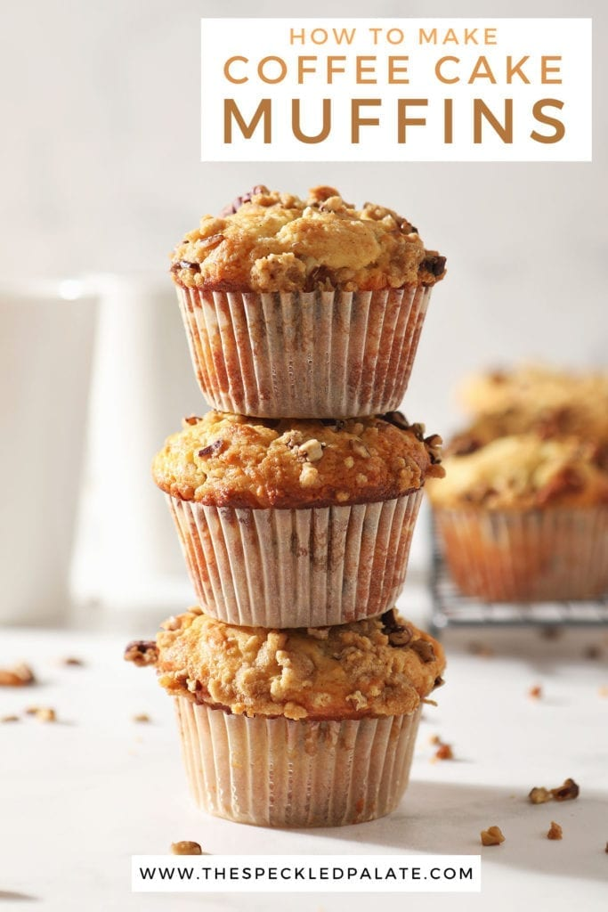 Three Coffee Cake Muffins are stacked on top of each other in front of a coffee mug and a wire cooling rack holding more muffins with the text 'how to make coffee cake muffins'