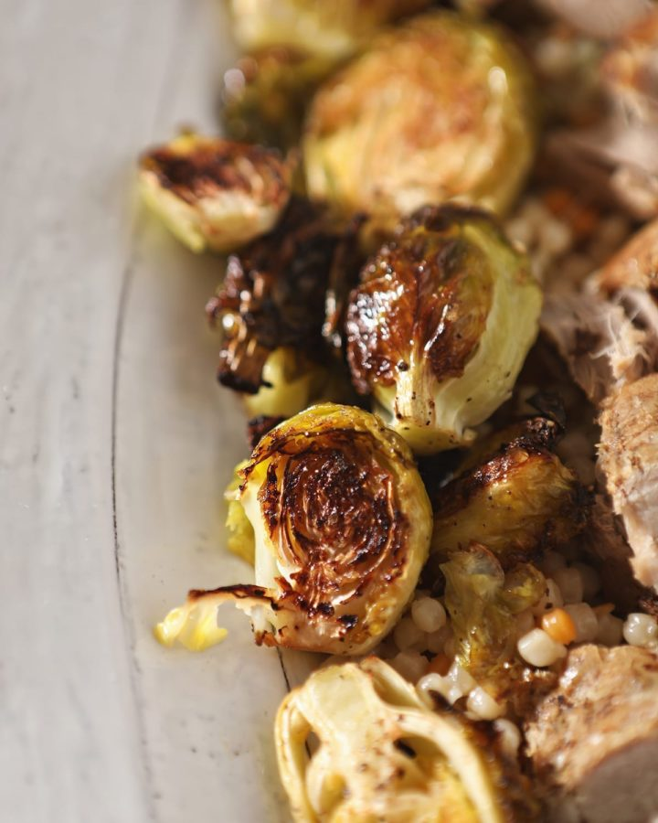 Close up of roasted brussels sprouts on a white serving tray with meat and couscous