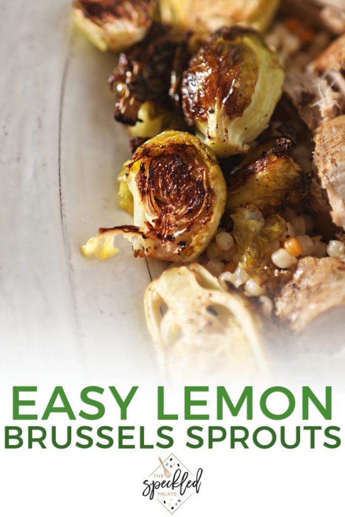 Close up of roasted brussels sprouts on a white serving tray with meat and couscous with the text 'easy lemon brussels sprouts'