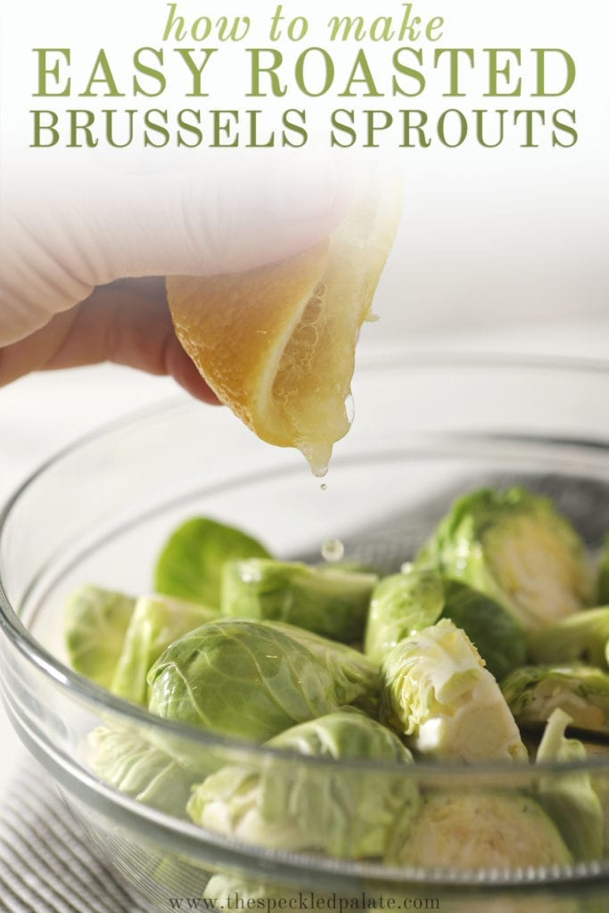 A hand squeezes a lemon on top of halved brussels sprouts in a glass bowl with the text 'how to make easy roasted brussels sprouts'