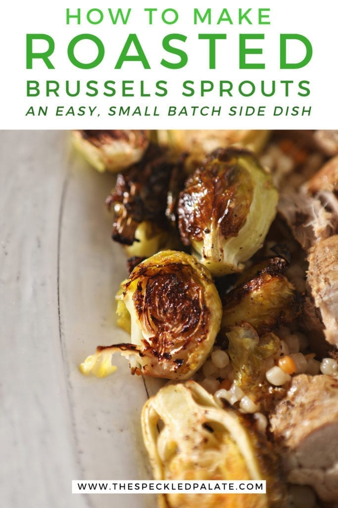 Close up of roasted brussels sprouts on a white serving tray with meat and couscous with the text 'how to make roasted brussels sprouts, an easy, small batch side dish'