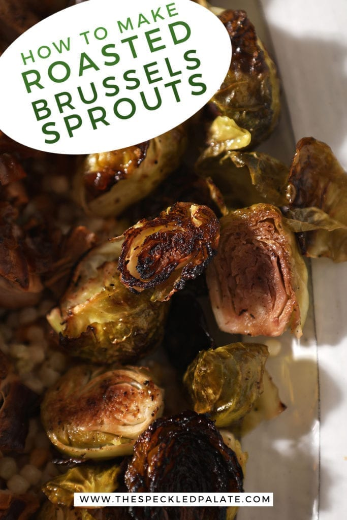 Close up of roasted brussels sprouts on a white serving tray with meat and couscous with the text 'how to make roasted brussels sprouts'