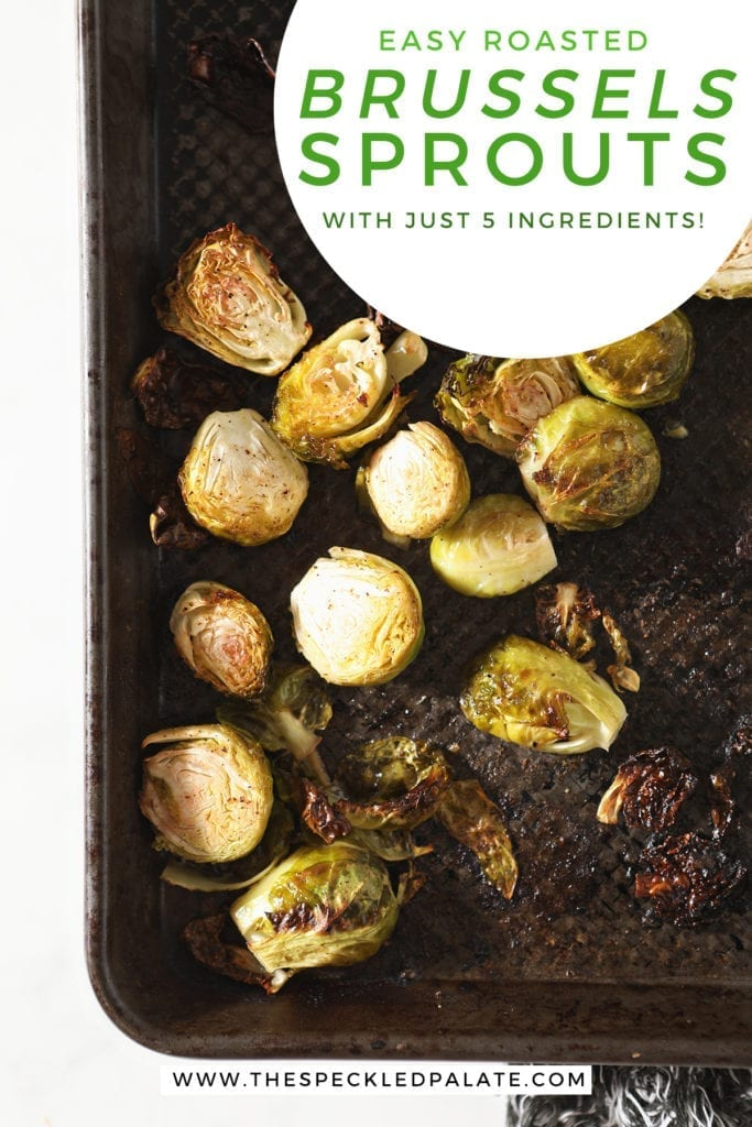Brussels sprouts on a baking sheet after baking with the text 'easy roasted brussels sprouts with just 5 ingredients'