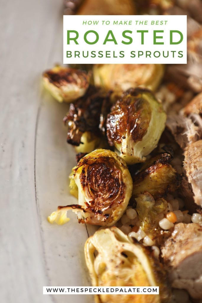 Close up of roasted brussels sprouts on a white serving tray with meat and couscous with the text 'how to make the best roasted brussels sprouts'