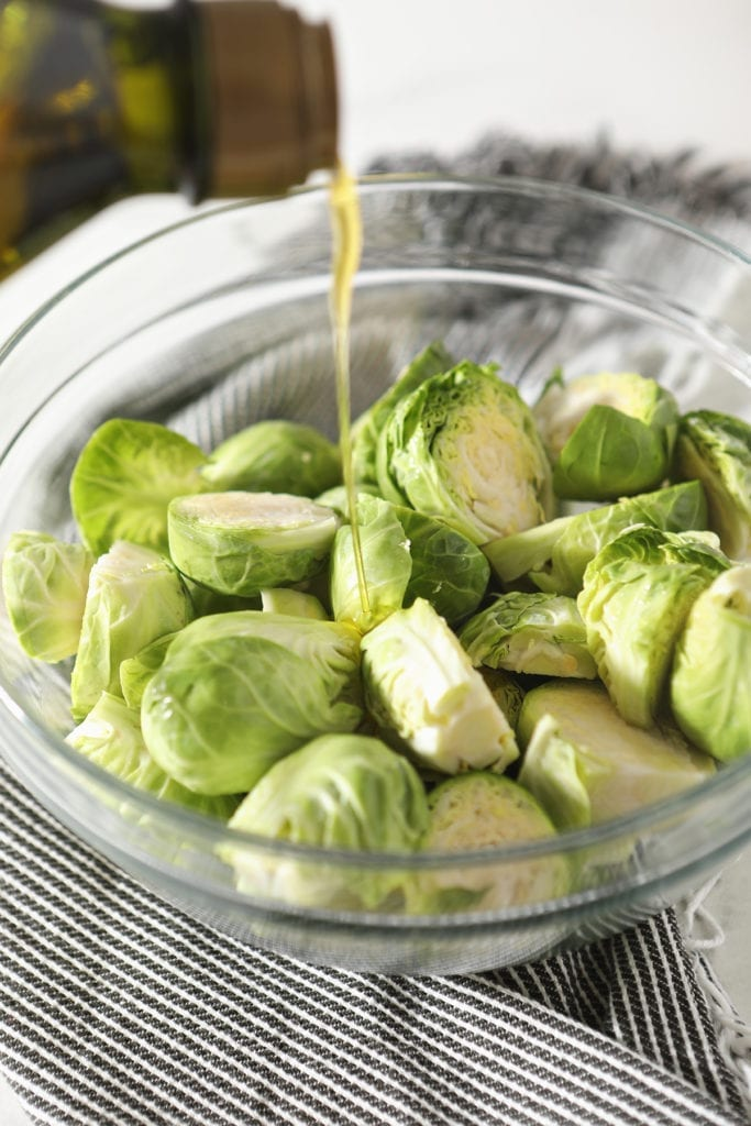 Olive oil drizzles on top of halved brussels sprouts in a glass bowl sitting on a gray striped towel