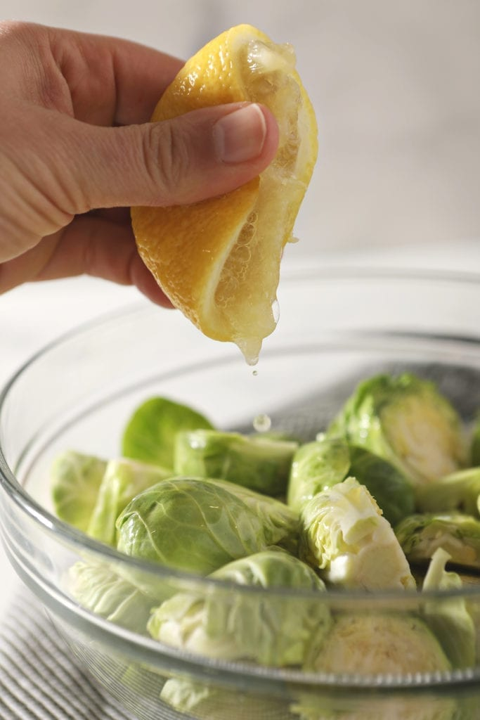A hand squeezes a lemon on top of halved brussels sprouts in a glass bowl