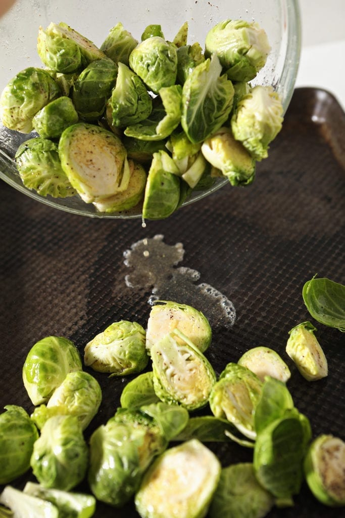 Halved brussels sprouts are dropped onto a hot baking sheet