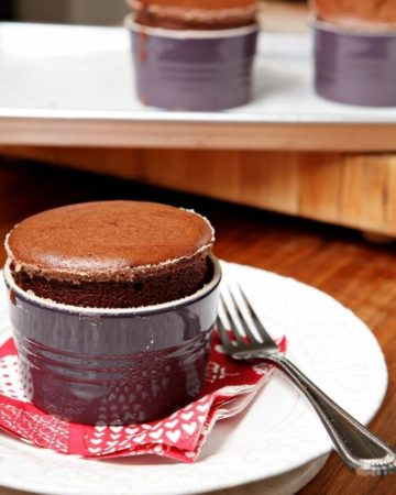 A souffle in a purple dish sits on a red napkin on a white plate in front of other souffles