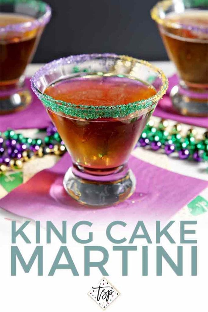 A dessert martini on a purple napkin, surrounded by festive mardi gras beads with the text 'king cake martini'